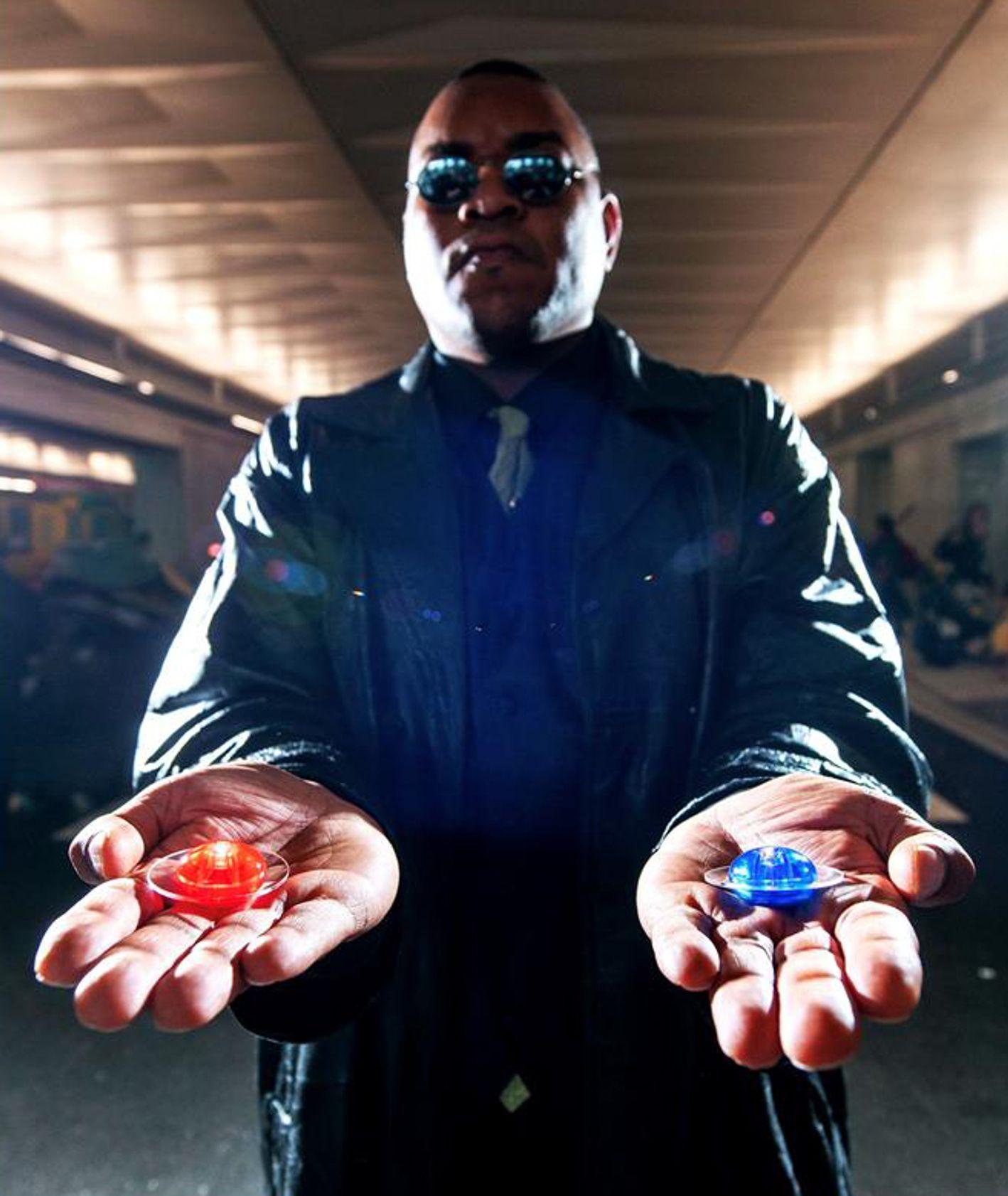 Kadr z filmu Matrix – Morfeusz z dwoma pigułkami – niebieską i czerwoną – w dłoni (fot. materiały prasowe)