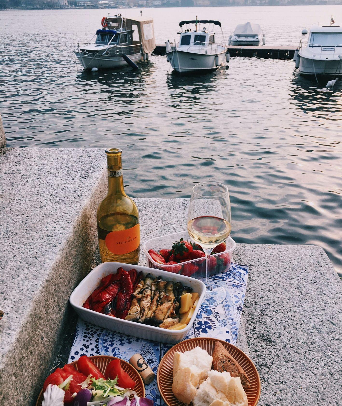 Włoskie wybrzeże, piknik nad rzeką – wino, pieczone warzywa, pieczywo, w tle zacumowane łódki (fot. Daria Litvinova)