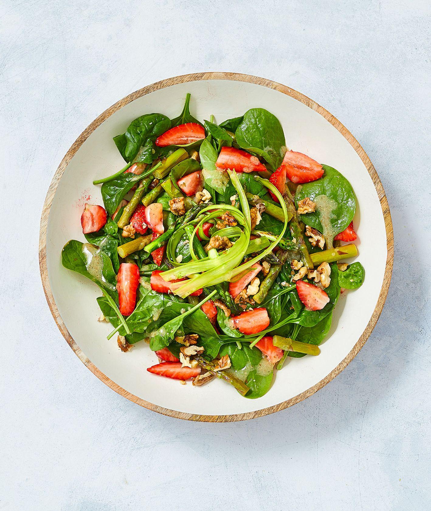 Lekka sałatka wiosennna z zieolnych szparagów ze szpinakiem baby i świeżymi truskawkami posypana orzechami włoskimi, podana z sosem vinegrette miodowo-musztardowym