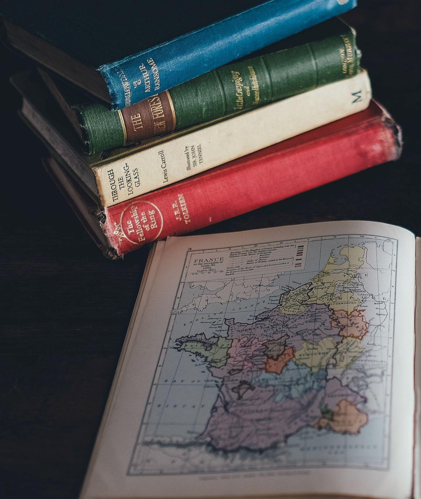 Cztery książki na stosie i jedna otwarta na stronie z mapą Francji (fot. Annie Spratt / unsplash.com)