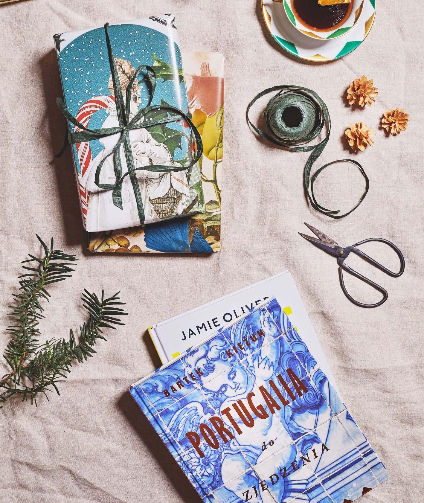 """Książki zapakowane w świąteczne papiery, nożyczki i tasiemki do pakowania prezentów, """"Wege"""" Jamiego Olivera i """"Portugalia"""" Bartka Kieżuna (fot. Maciej Niemojewski)"""