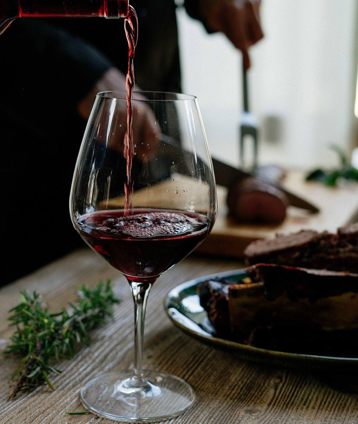 Napełnianie winem kieliszka podczas posiłku (fot. Lefteris Kallergis / unsplash.com)