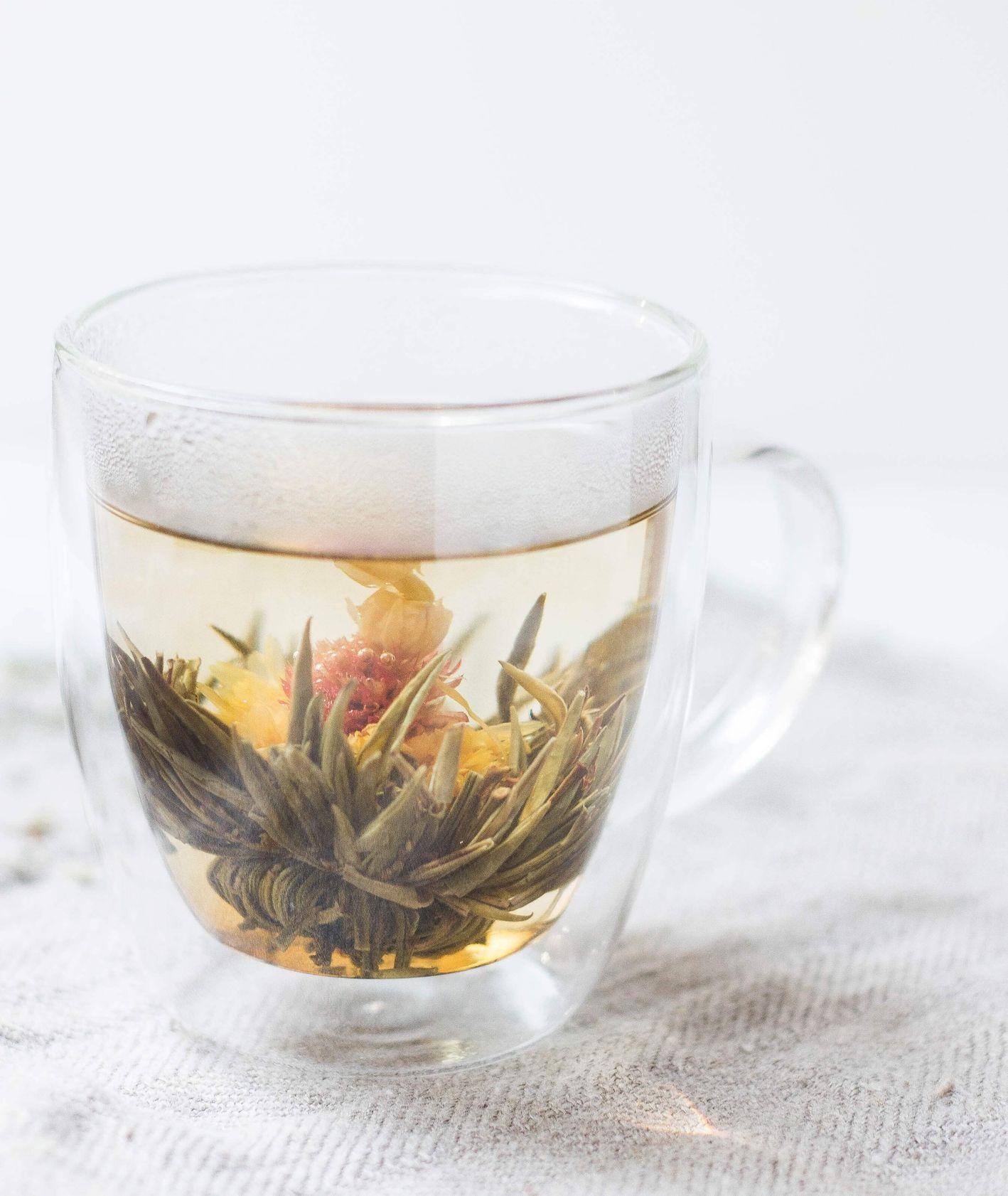 Kubek zielonej herbaty na białym płótnie w szklanym kubku. (fot. Alison Marras / unsplash.com)