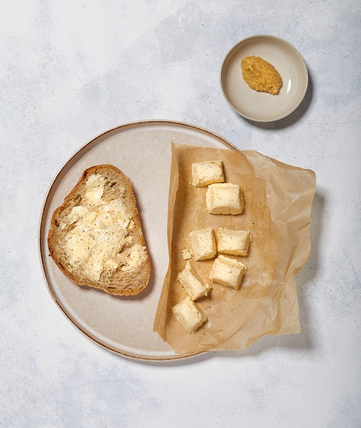 Pikantne masło musztardowe na kanapki podane na kromce domowego chleba pszennego