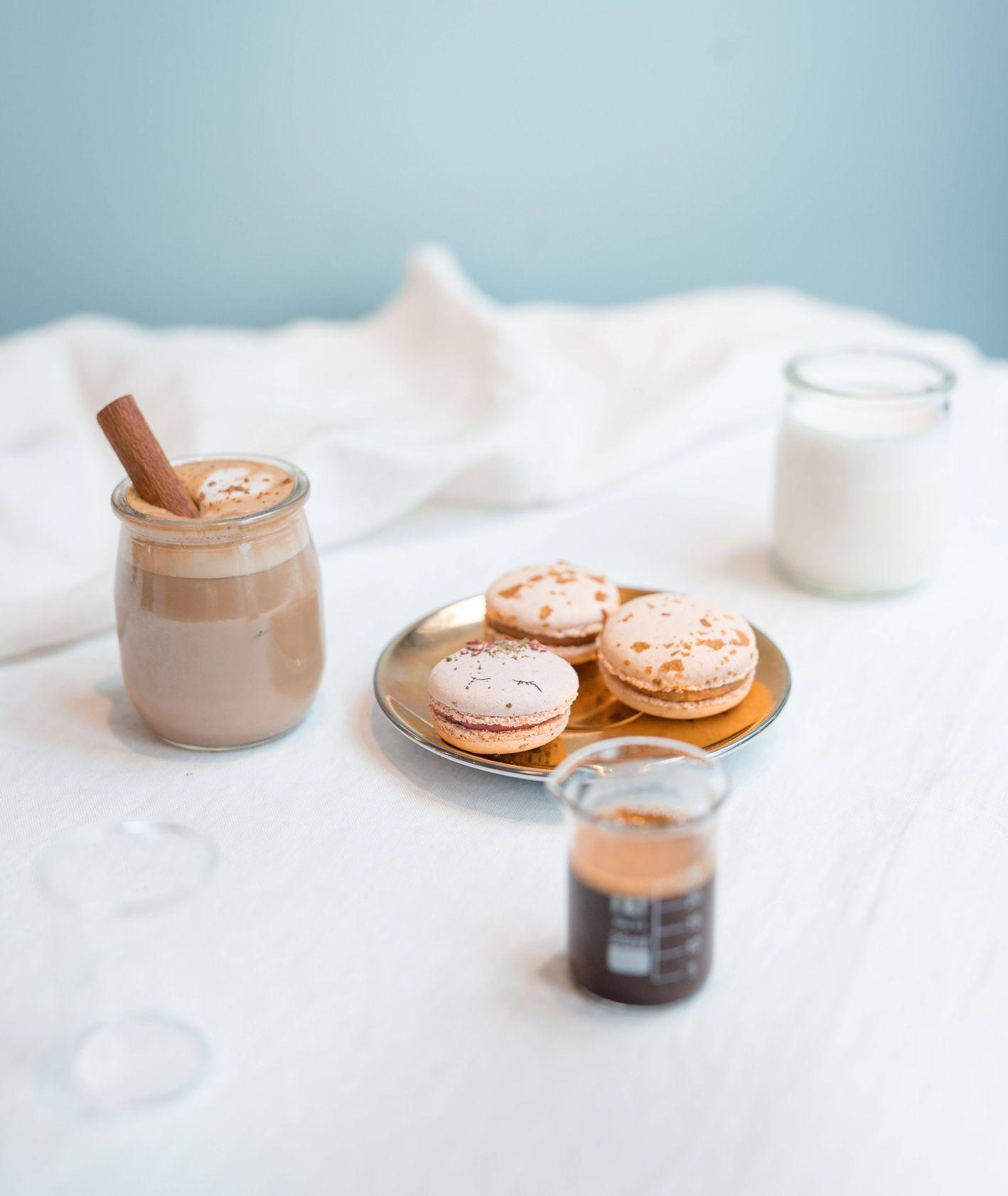 Cappuccino z cynamonem, makaroniki, mleko i espresso na białym obrusie (fot. Martyna Cybuch)
