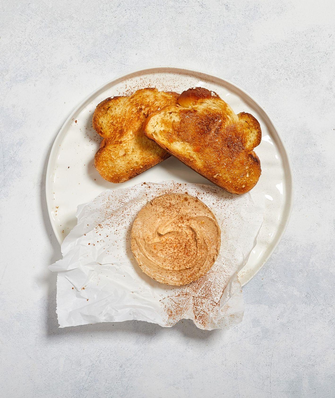 Słodkie masło cynamonowe z dodatkiem miodu i skórki z pomarańczy podane na zgrillowanej kromce chałki
