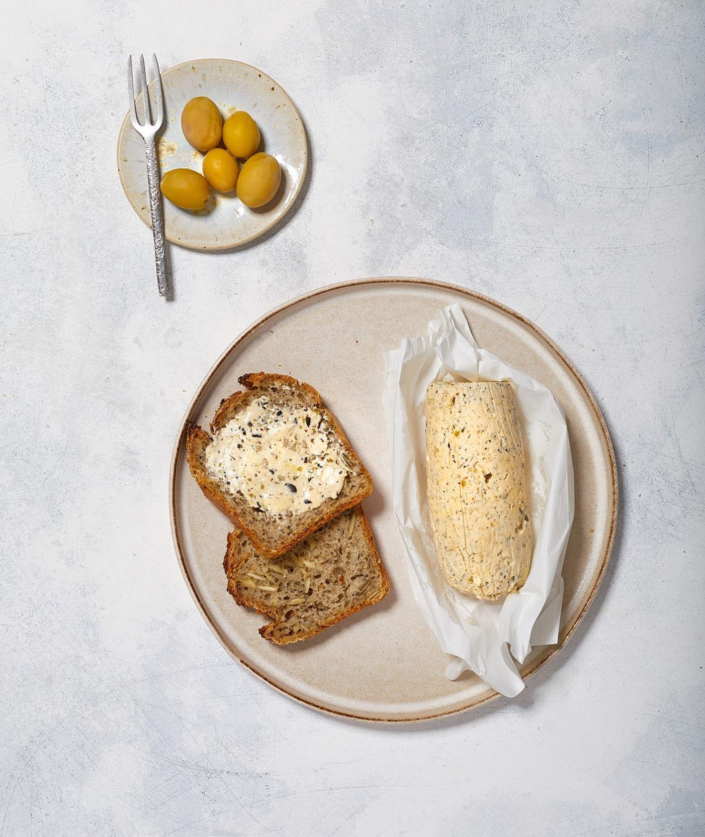 Pikantne masło oliwkowe z czosnkiem i ostrą paryką podane na kromce żytnego chleba na zakwasie