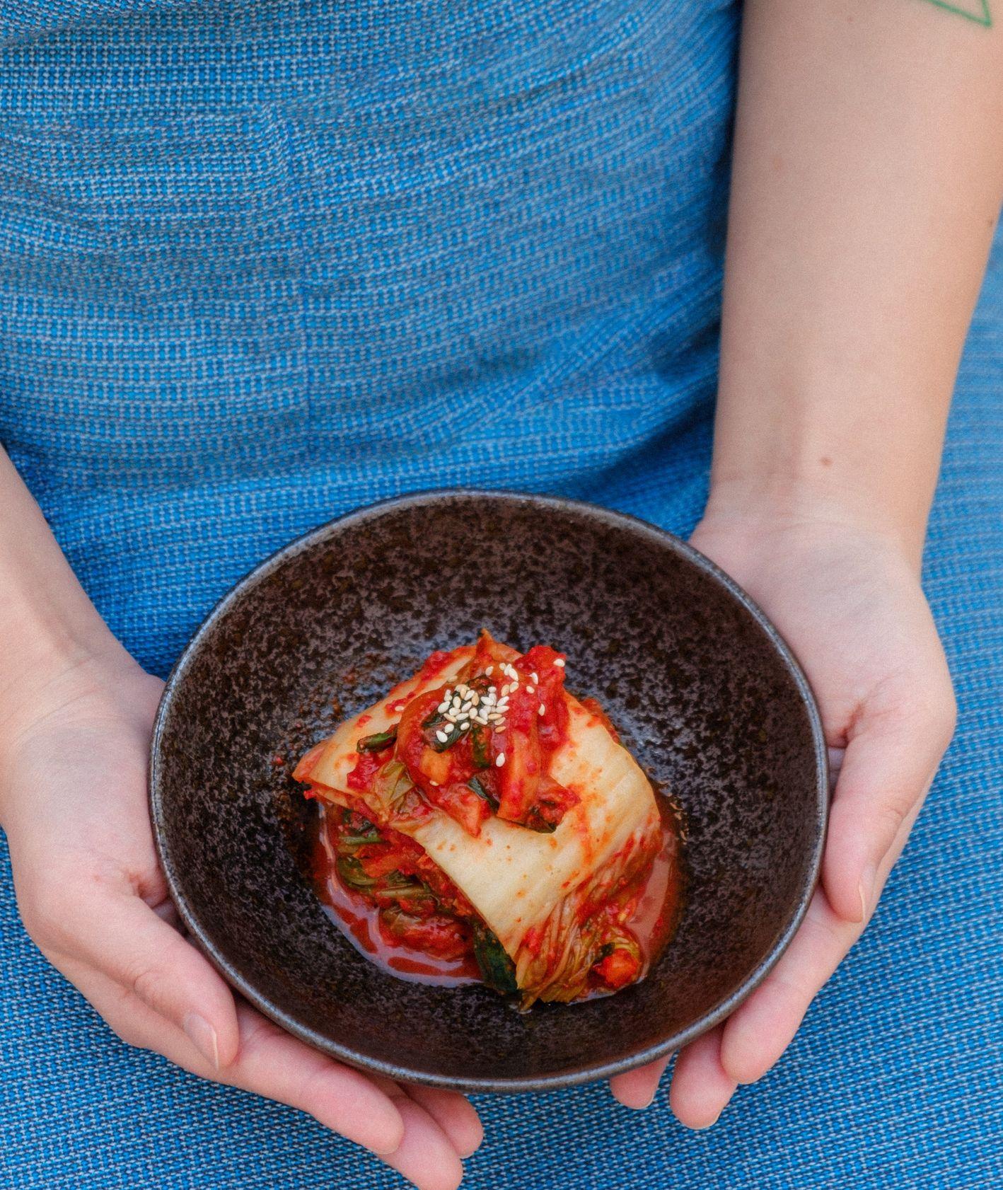 Kobieta trzymająca talerz z kimchi (fot. Portuguese Gravity / unsplash.com)