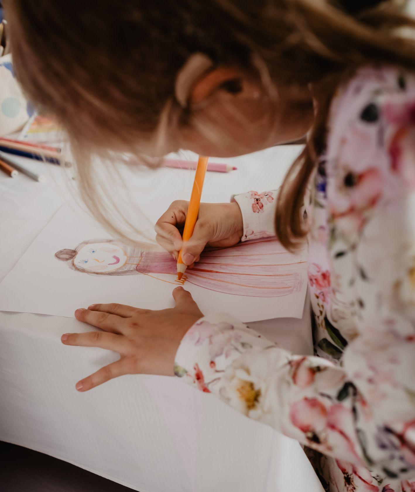 Dziewczynka rysująca kredkami (fot. Victoria Priessnitz / unsplash.com)