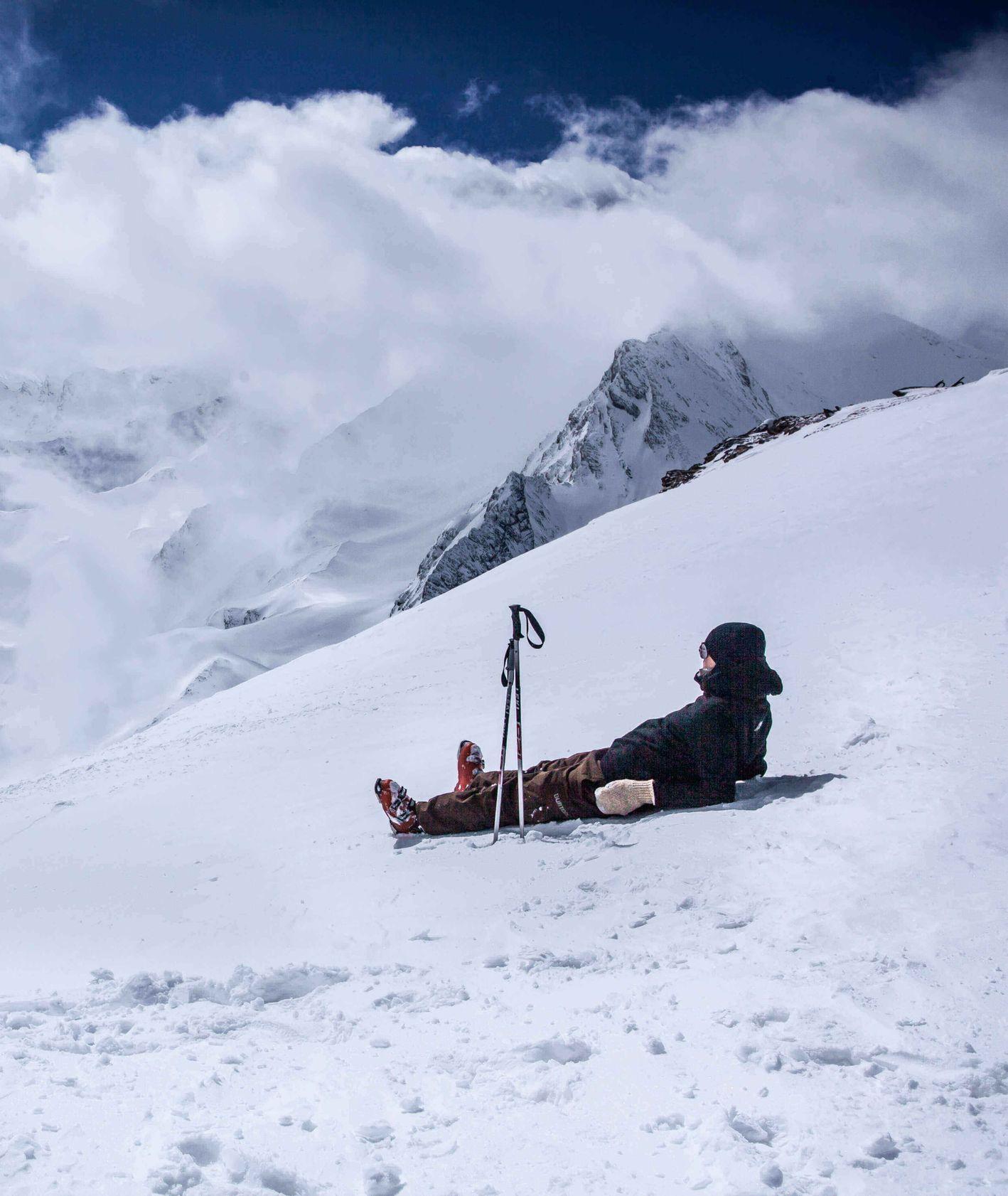 Mężczyzna w kombinezonie narciarskim leżący na stoku