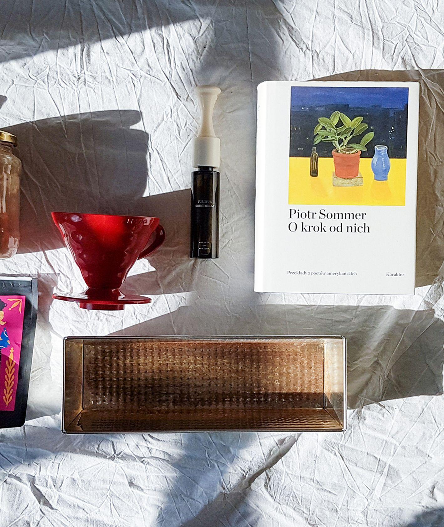 """Kubek, zakwas, drip, książka Piotra Sommera """"O krok od nich"""", opakowanie kawy, keksówka i liść monstery (fot. Maciek Kostrzewa)"""