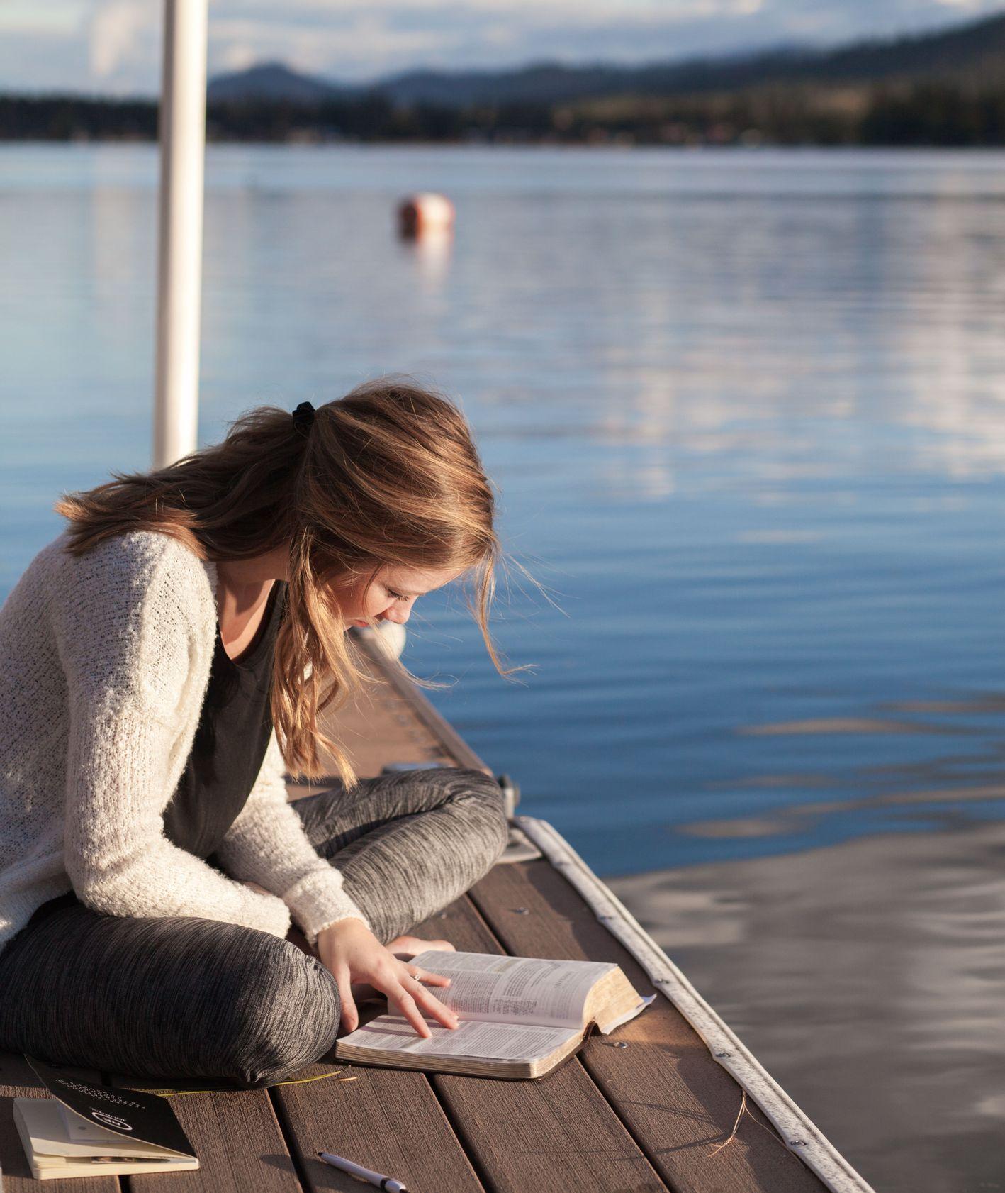 Kobieta czytająca książkę nad jeziorem, sierpniowe aktywności, czytanie książki w plenerze (fot. Bethany Laird / unsplush.com)
