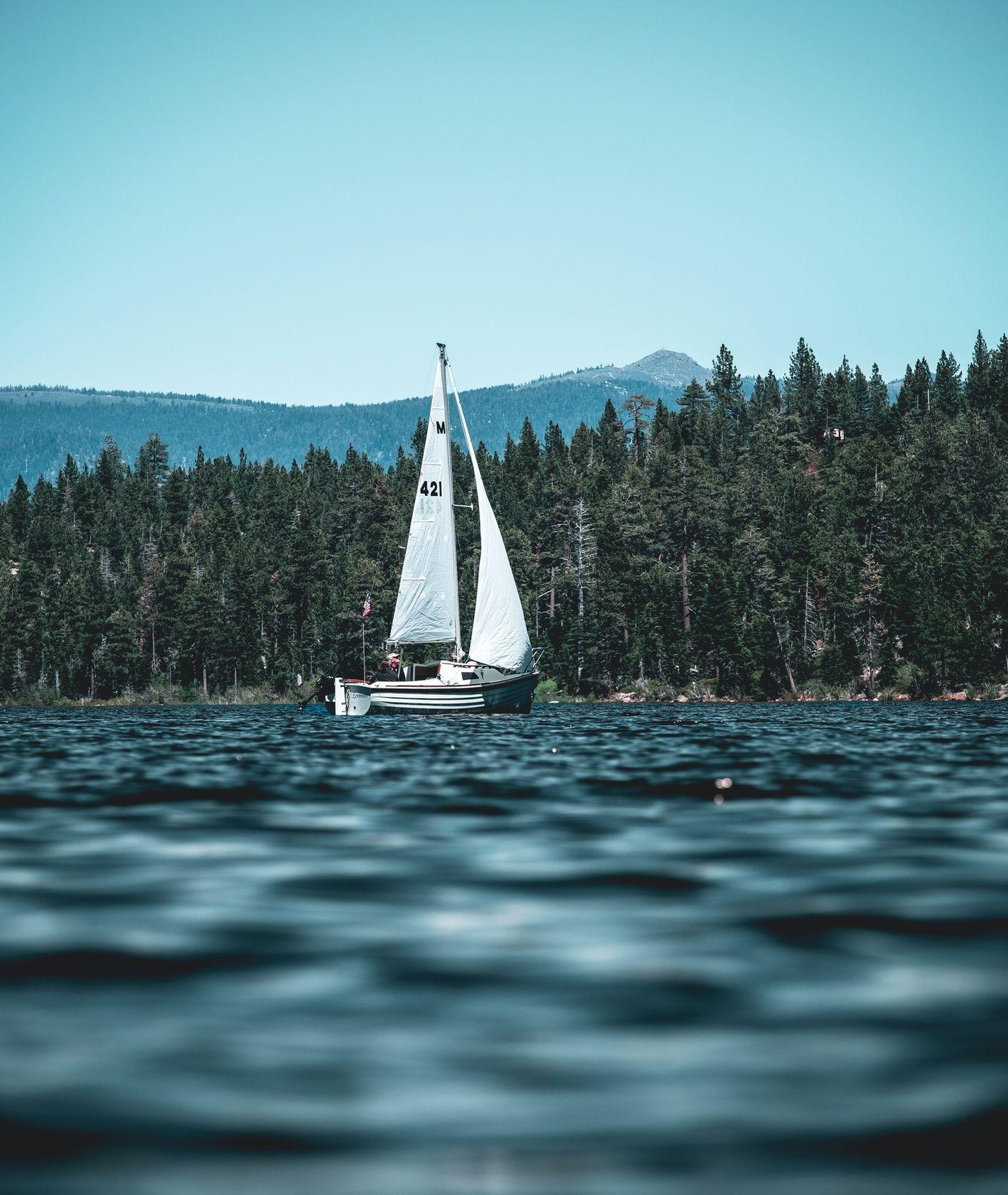 Żaglówka z białym żaglem na jeziorze (fot. Chris Maestas / unsplash.com)