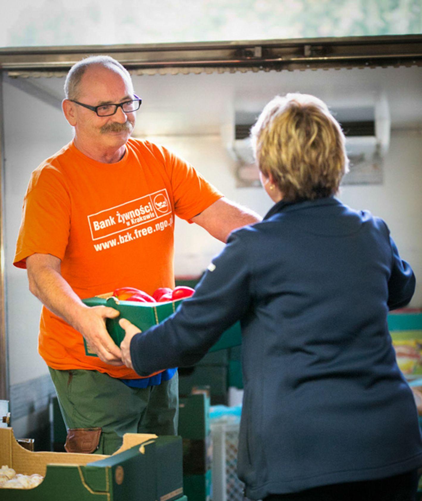 Mężczyzna przekazuje kobiecie karton z paprykami (fot. materiały prasowe)
