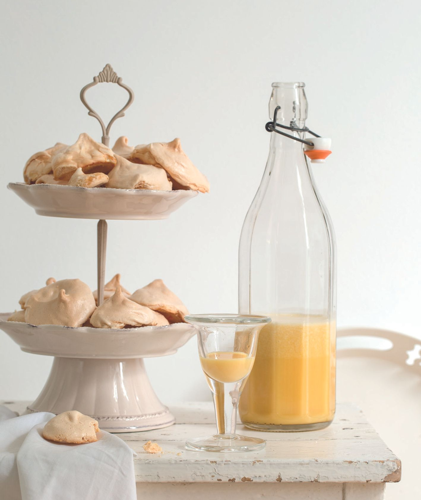 Butelka domowego ajerkoniaku, kremowy ajerkoniak w kieliszku, patera a bezami (fot. dinnershow studio)