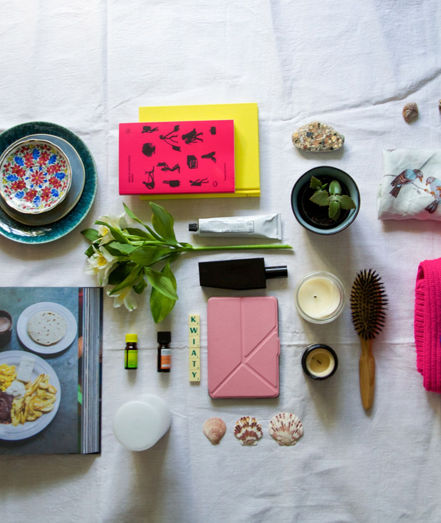 Naczynia, książki, ubrania, szczotka do włosów, książka, rośliny, olejki zapachowe, świeczki, kosmetyki i dyfuzor ułożone w kompozycji (fot. Anna Czajkowska)