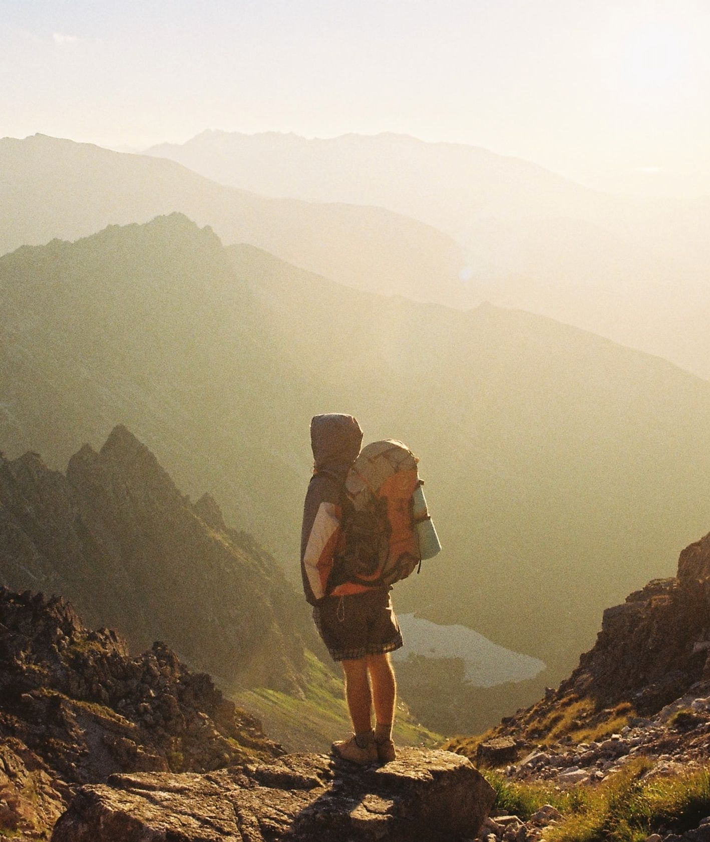 Mężczyzna z plecakiem stojący w górach (fot. Danka Peter / unsplash.com)