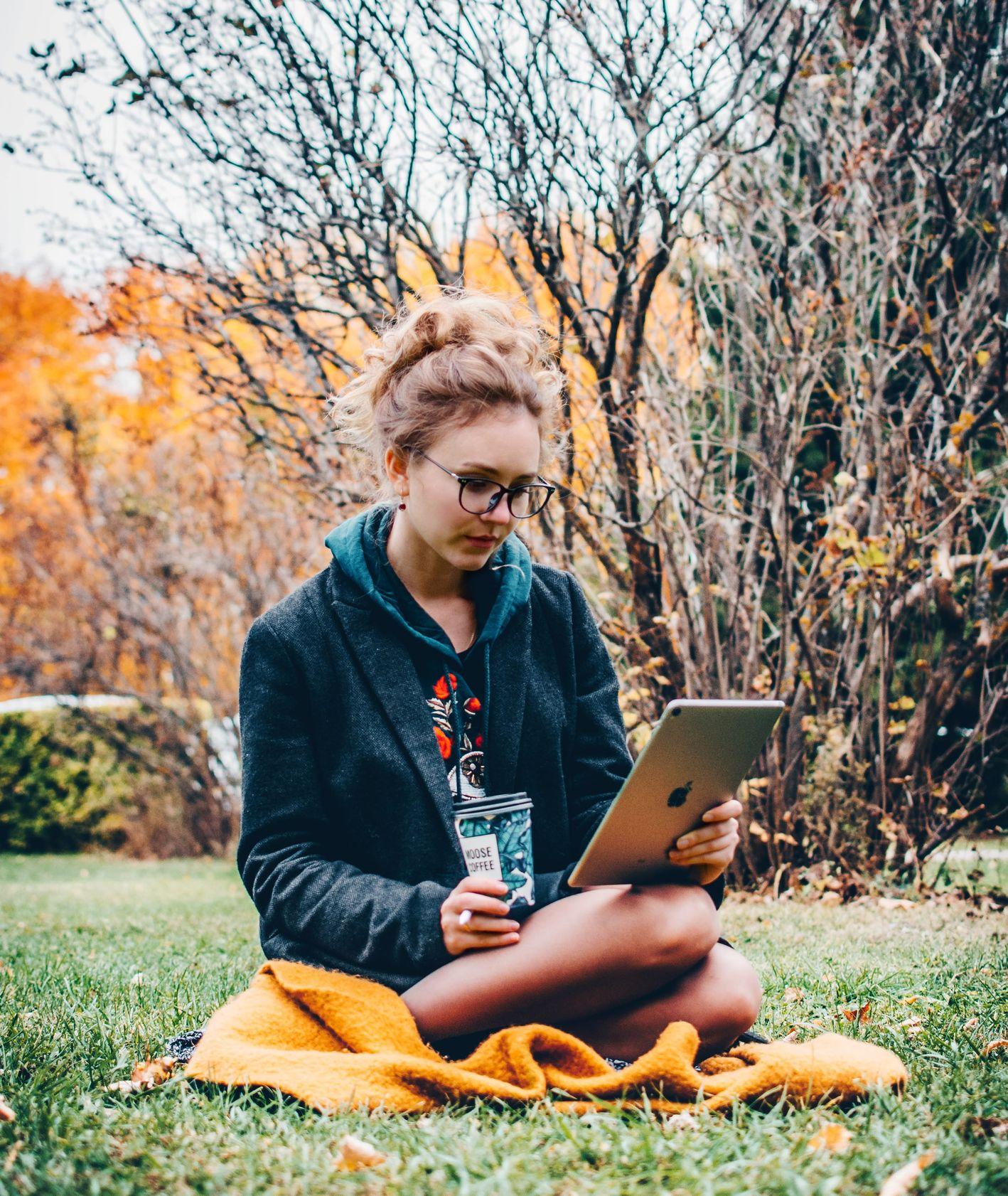 Dziewczyna czytająca ebook w ogrodzie (fot. Nikita Katsevich / unsplash.com)