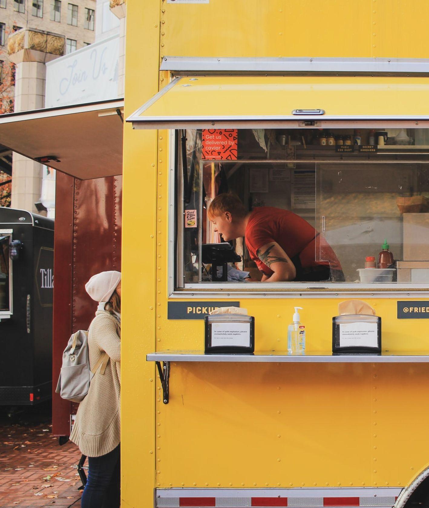 Żółty food truck z jedzeniem (fot. Karen Zeng / unsplash.com)