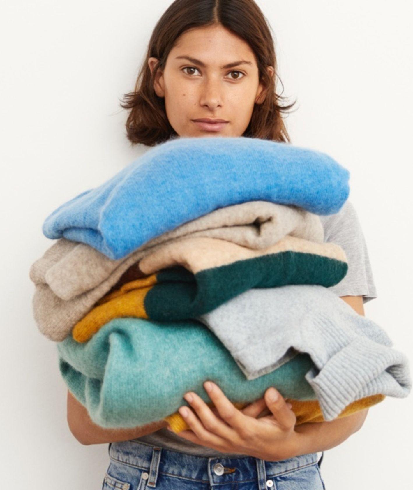 Kobieta trzymająca wełniane swetry (fot. materiały prasowe)