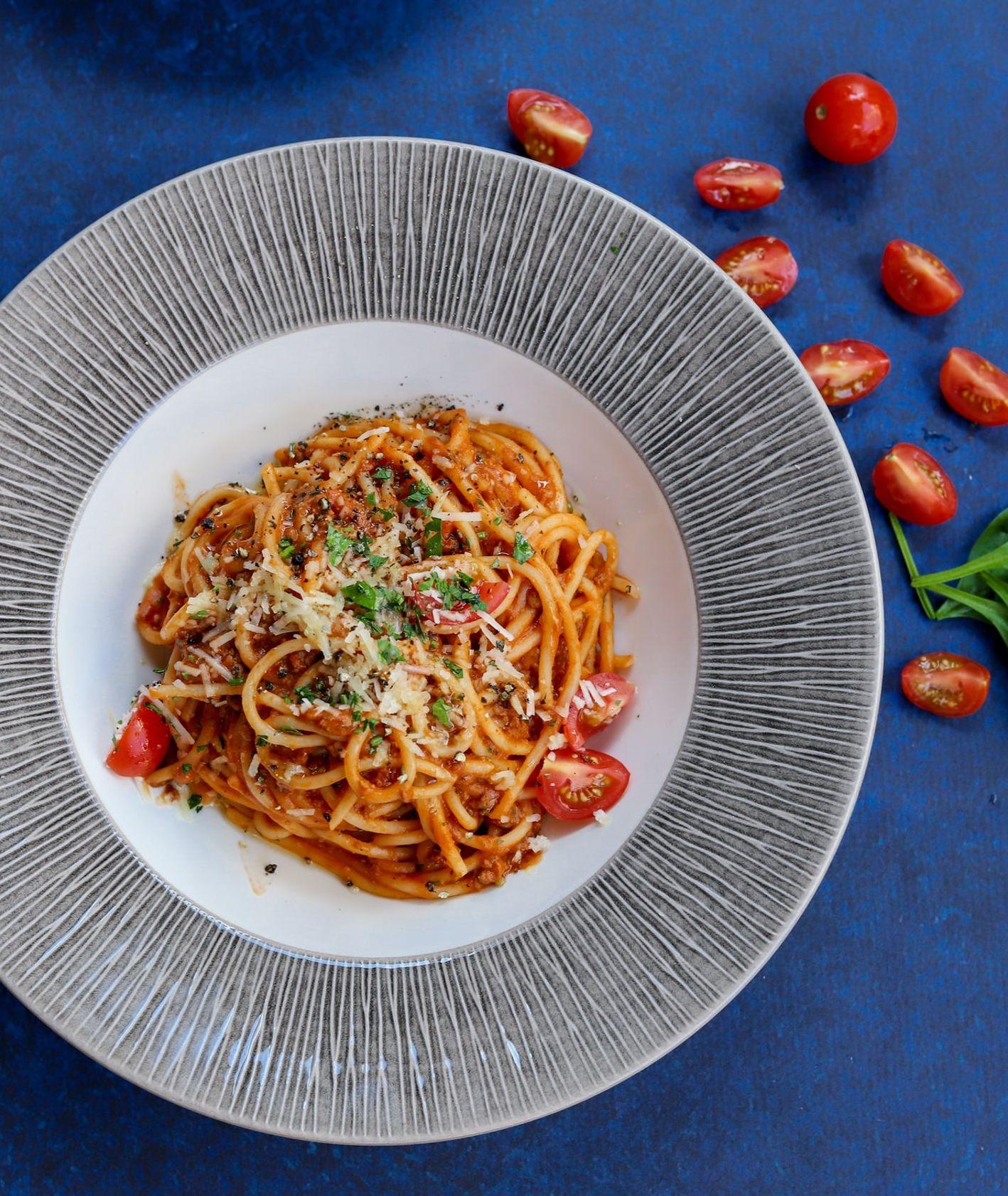 Proste spaghetti pomidorowe z bazylią i parmezanem na niebieskim obrusie (fot. Danijela Prijovic / unsplash.com)