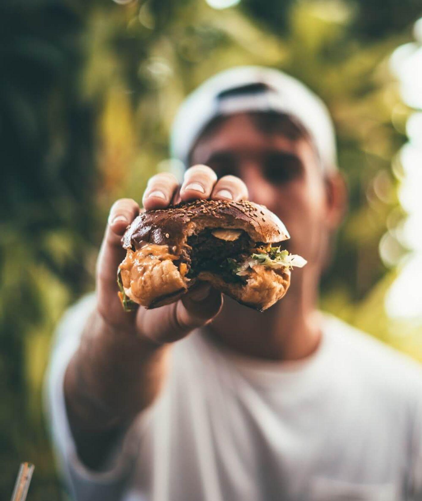Mężczyzna z hamburgerem : Oliver Sjöström : Unsplash.com.jpg