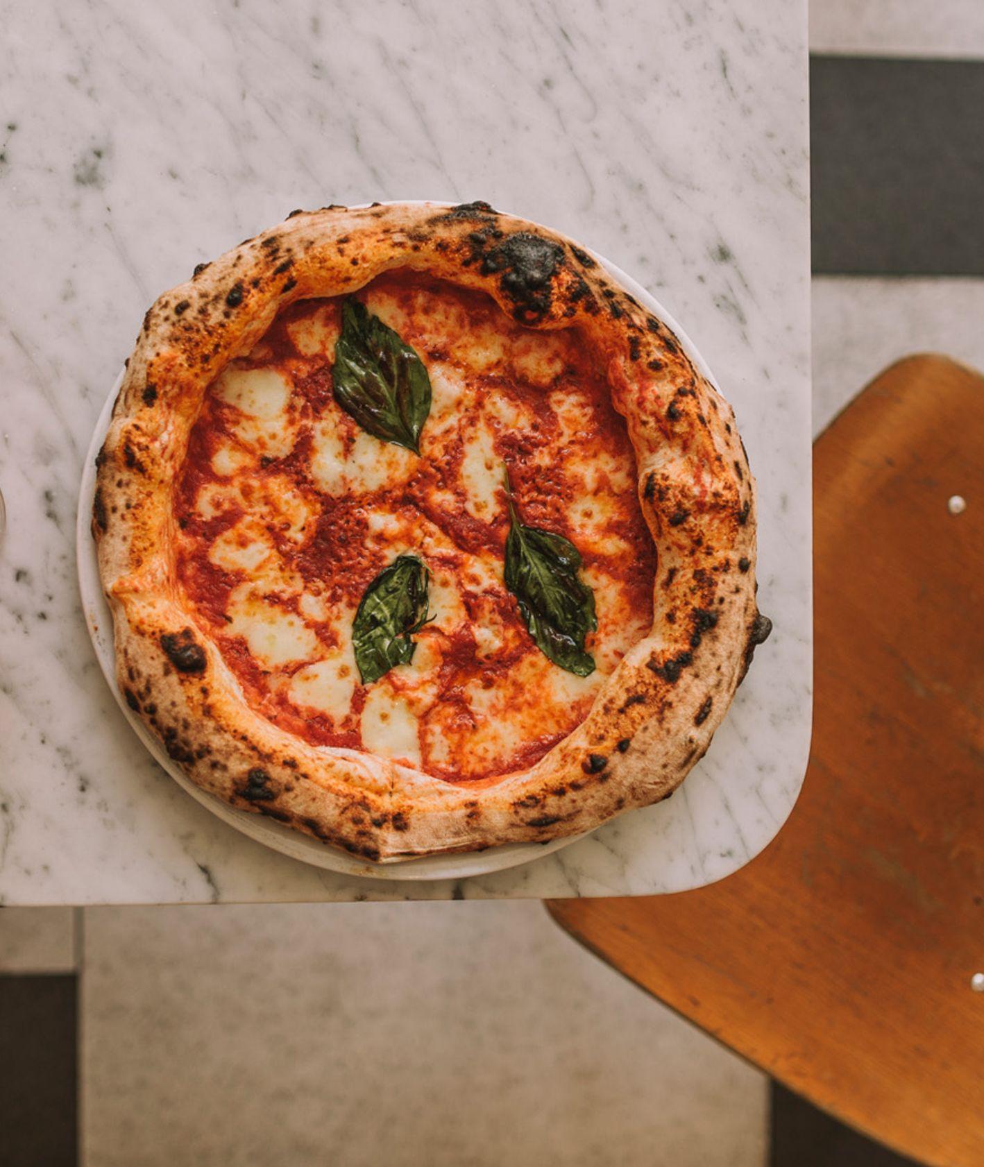 Pizza z bazylią, krzesło, blat marmurowy