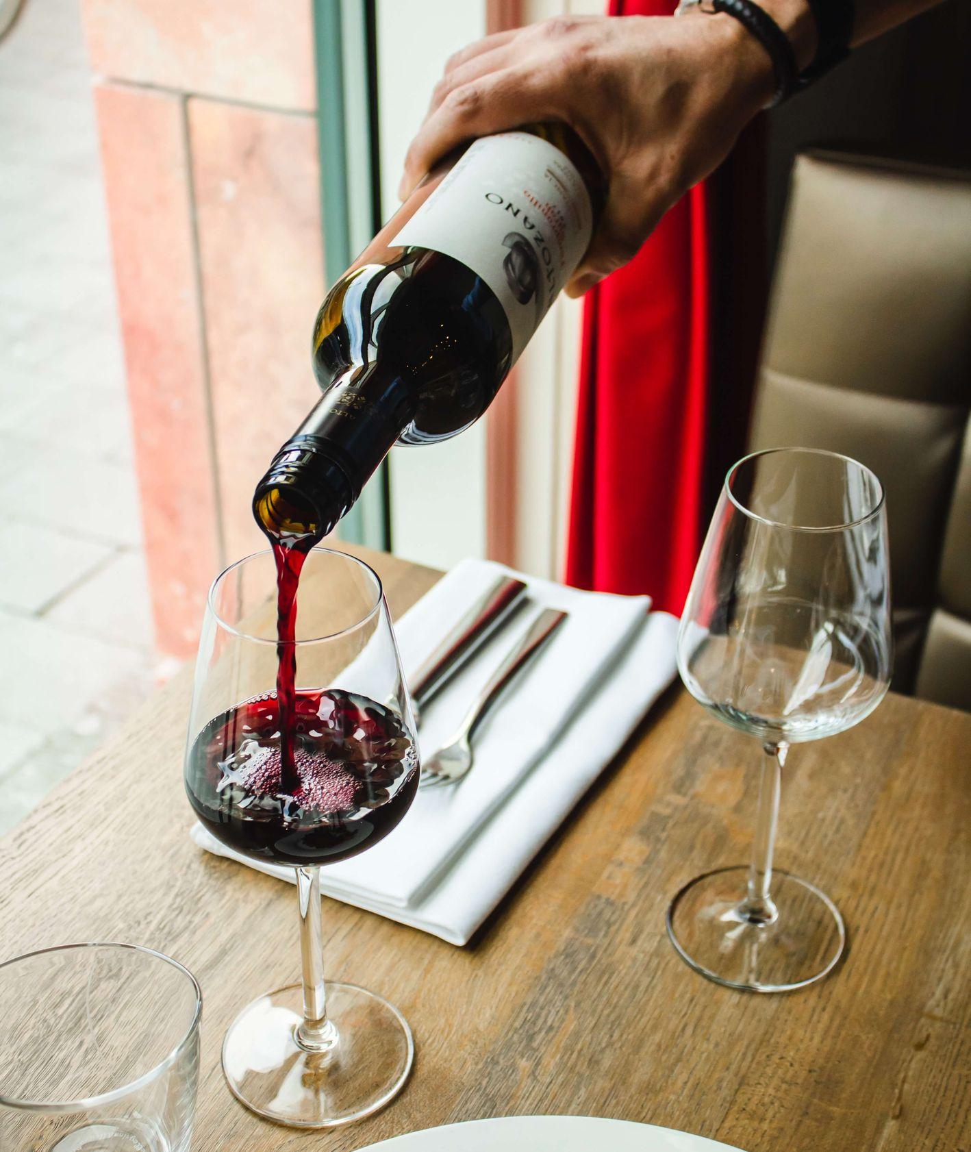 Mężczyzna nalewający czerwone wino do kieliszka (fot. Louis Hansel / unsplash.com)