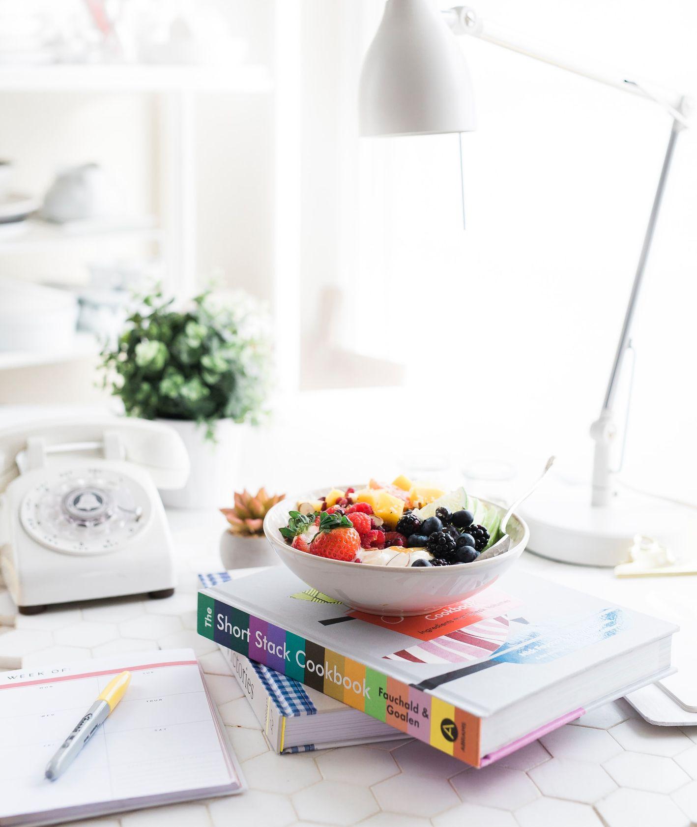 książka kucharska z położoną na niej miską owoców