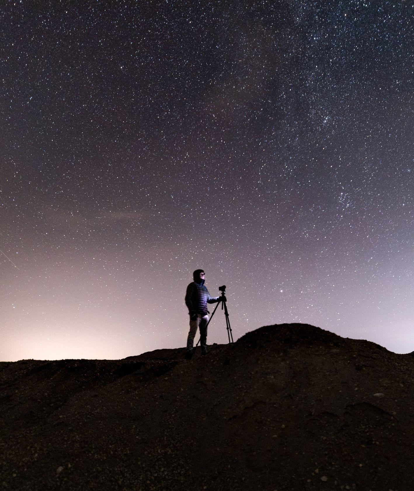 Człowiek z aparatem na tle gwiazd w górach (fot. Vincent Ledvina / unsplash)