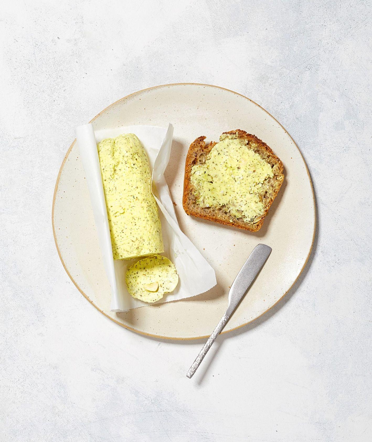 Domowe masło czosnkowe z ziołami prowansalskimi i ze szczyptą kurkumy podane na grzance z chleba razowego