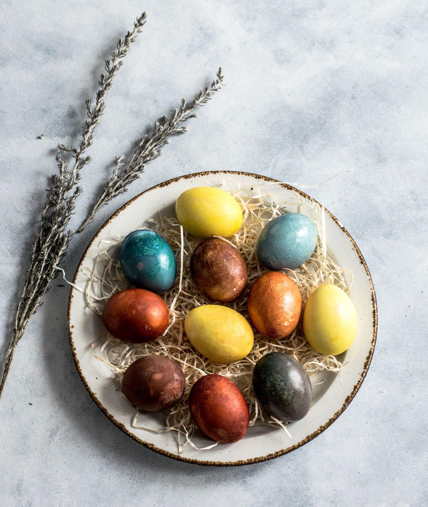 Wielkanocne jajka na tależu ozdobione gałązką. (fot. Monika Grabkowska / unsplash.comn)