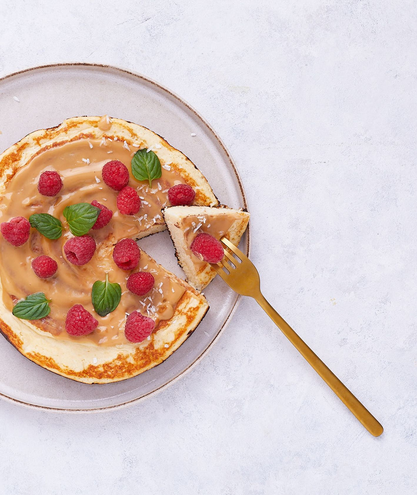 Puszysty omlet twarogowy z sosem orzechowym i malinami na talerzu (fot. Maciek Niemojewski)