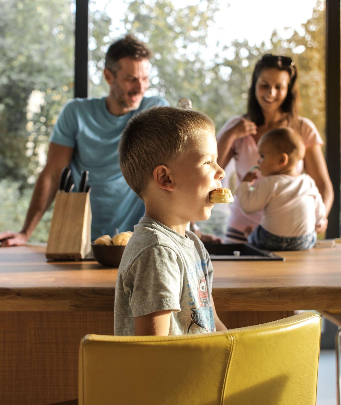 Dzieci jedzą słodycze z rodzicami w kuchni (fot. Cottonbro / pexels.com)