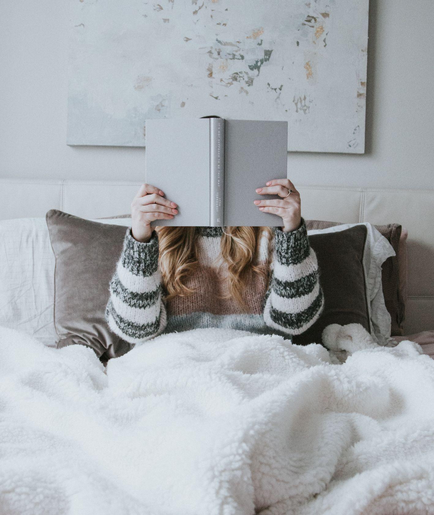 Kobieta czytająca książkę w łóżku (fot. David Lezcano / unsplash.com)