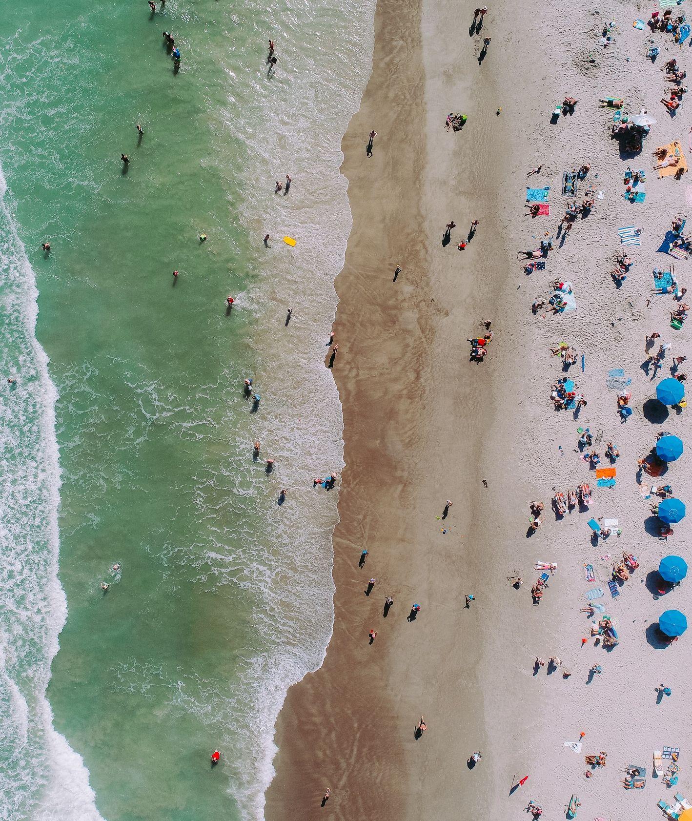 Ludzie na plaży i w morzu, z lotu ptaka (fot. Clement Chen / unsplash.com)