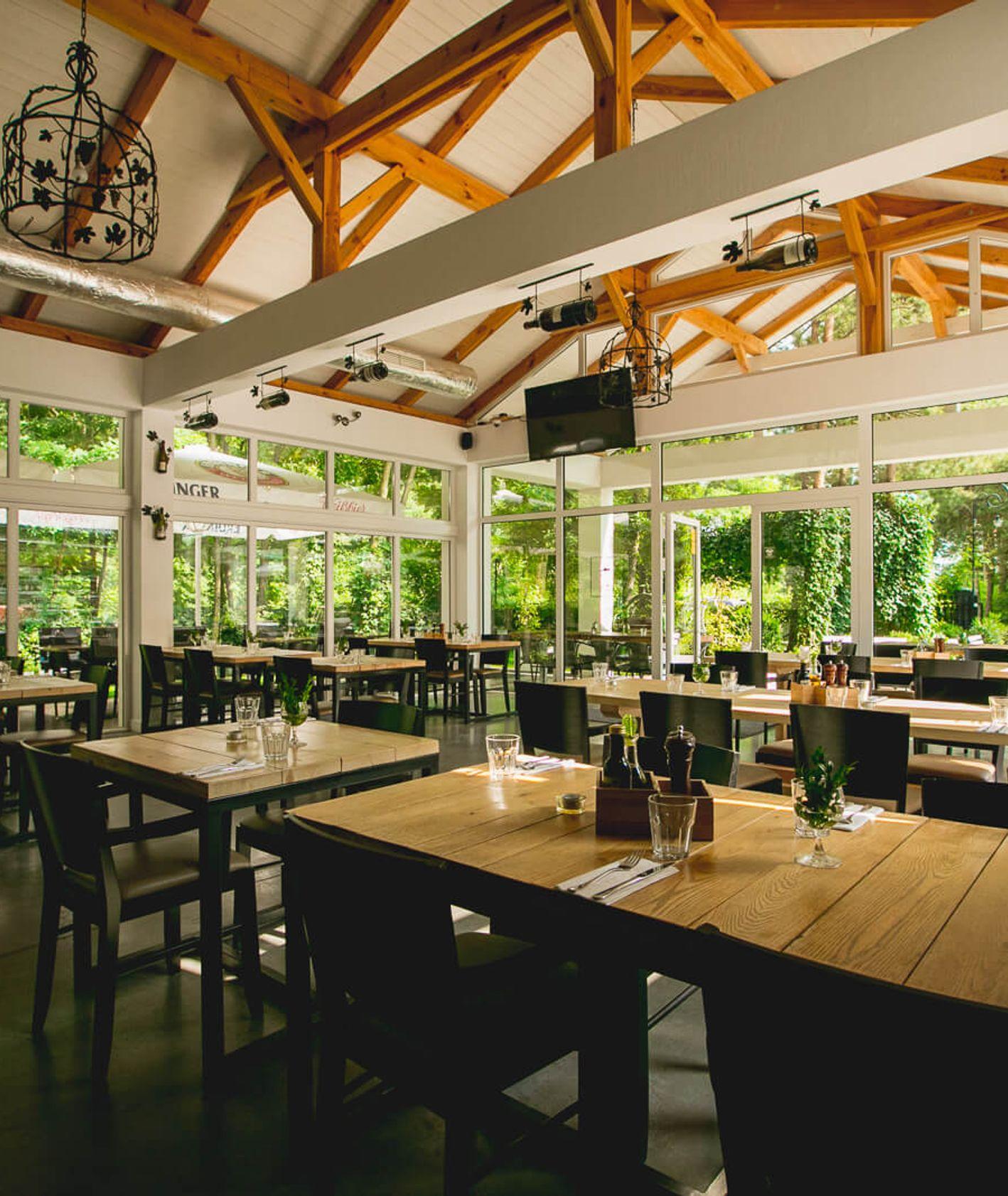 Sala wypełniona stołami, drewniany strop- elegancki wystrój restauracji Winny garaż.