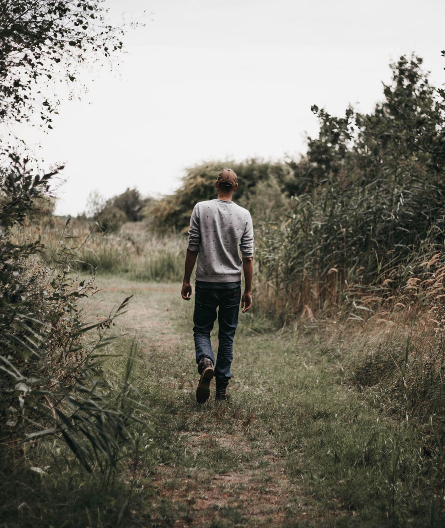 Mężczyzna idący ścieżką między roślinami (fot. Isaac Mehegan / unsplash.com)