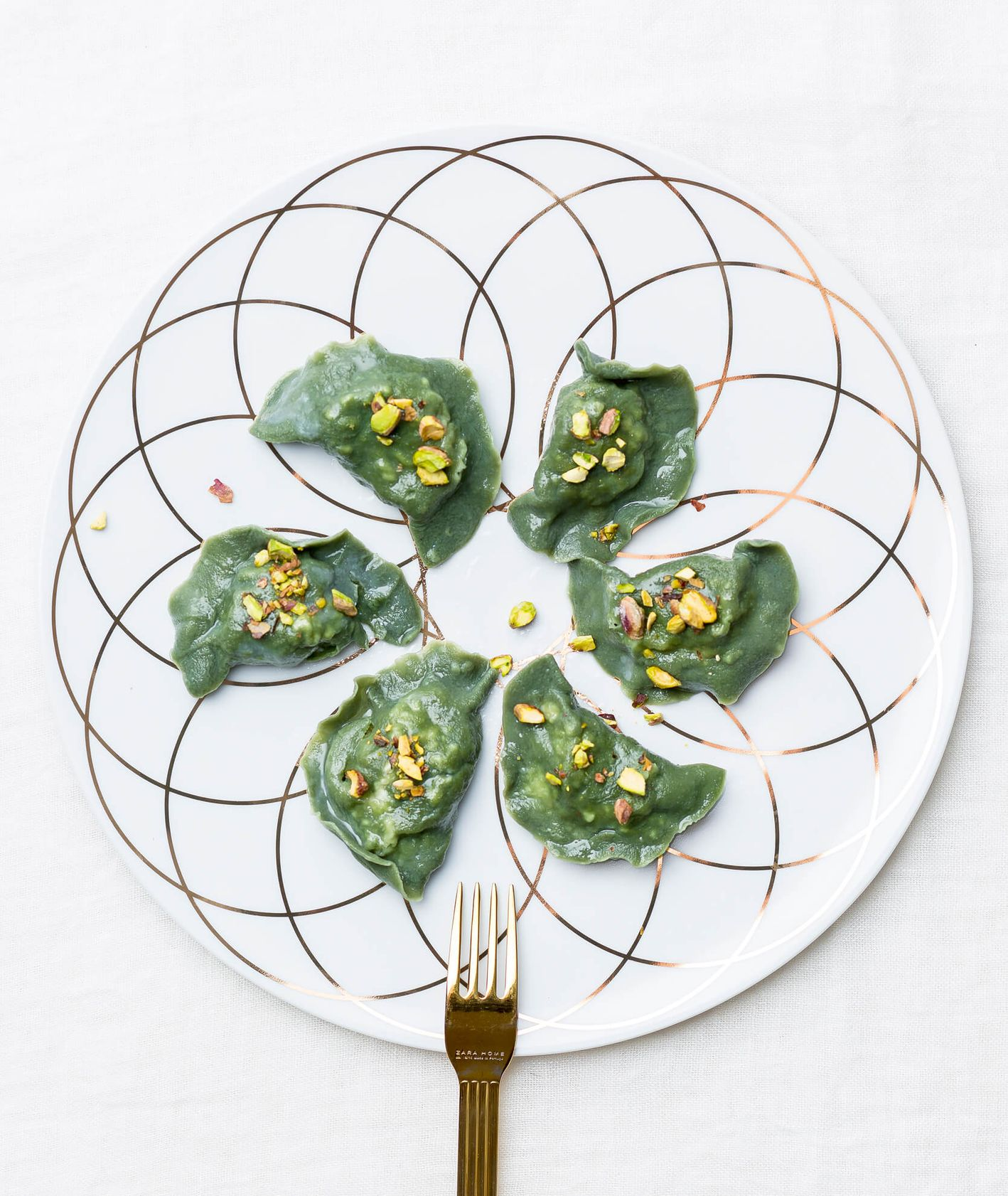 Zielone pierogi posypane pistacjami
