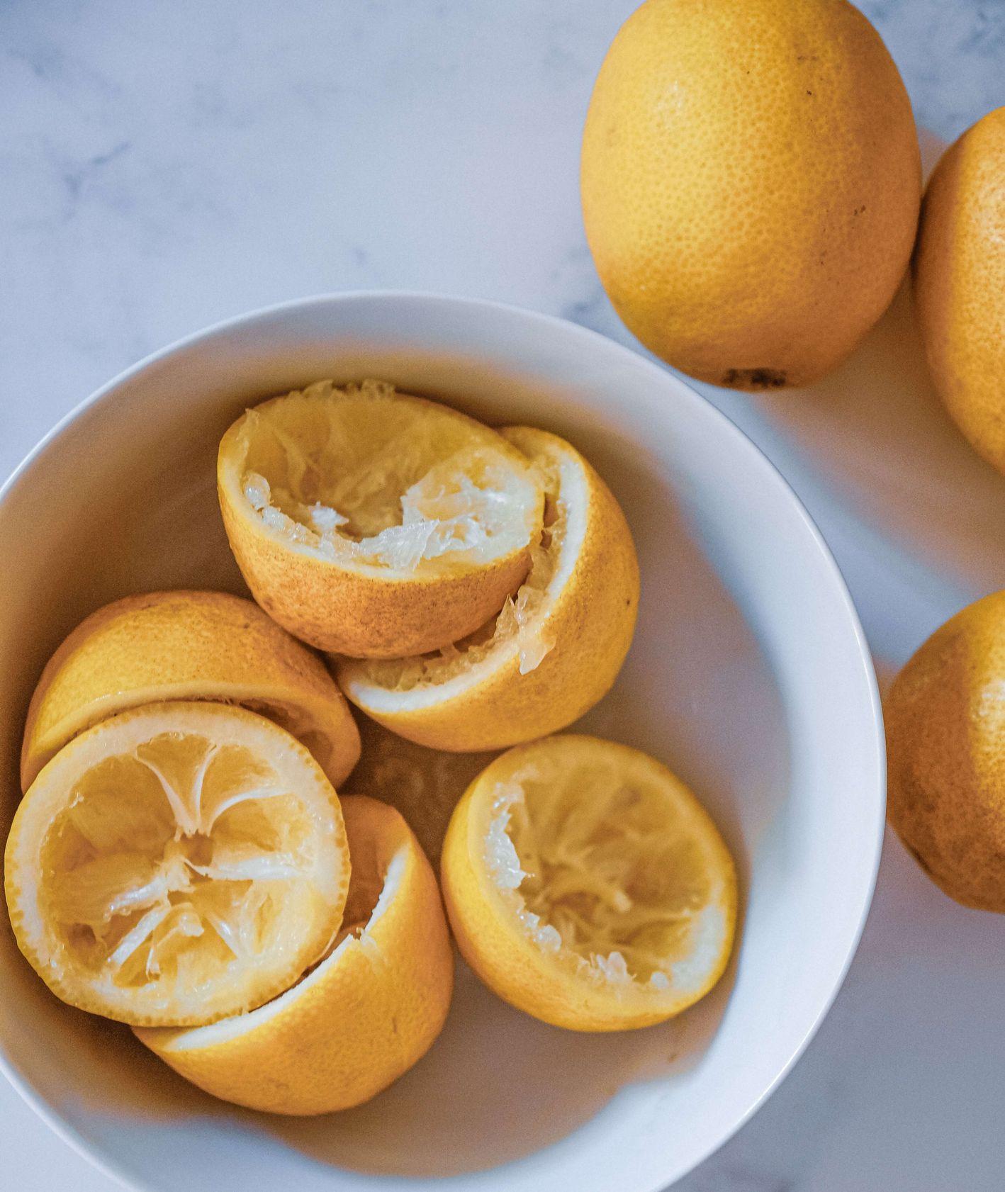 Skórki po wyciśniętych cytrynach w miseczce, całe cytryny, unsplash Jeff Siepman