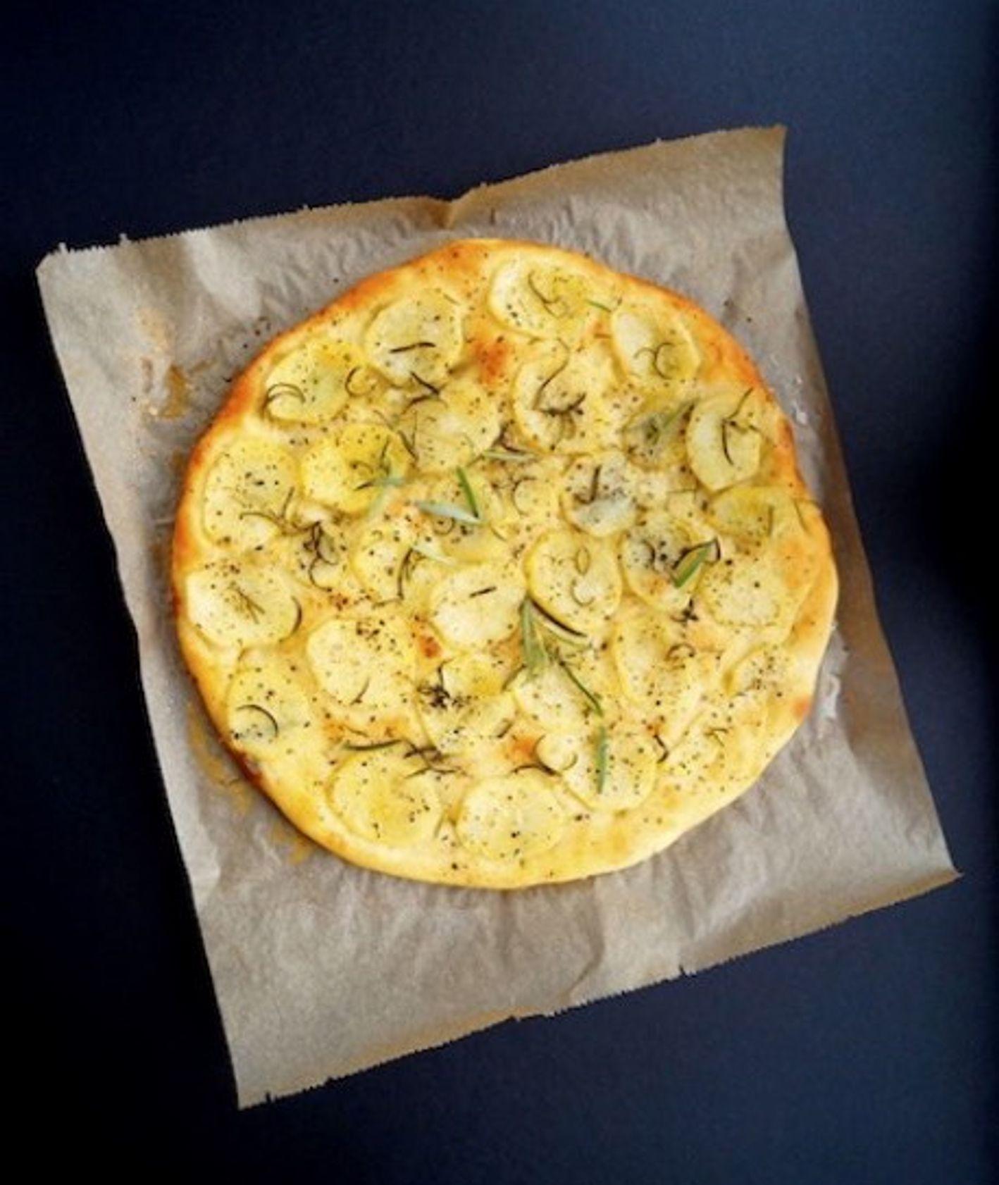 Focaccia z rozmarynem i ziemniakami leżąca na papierze do pieczenia