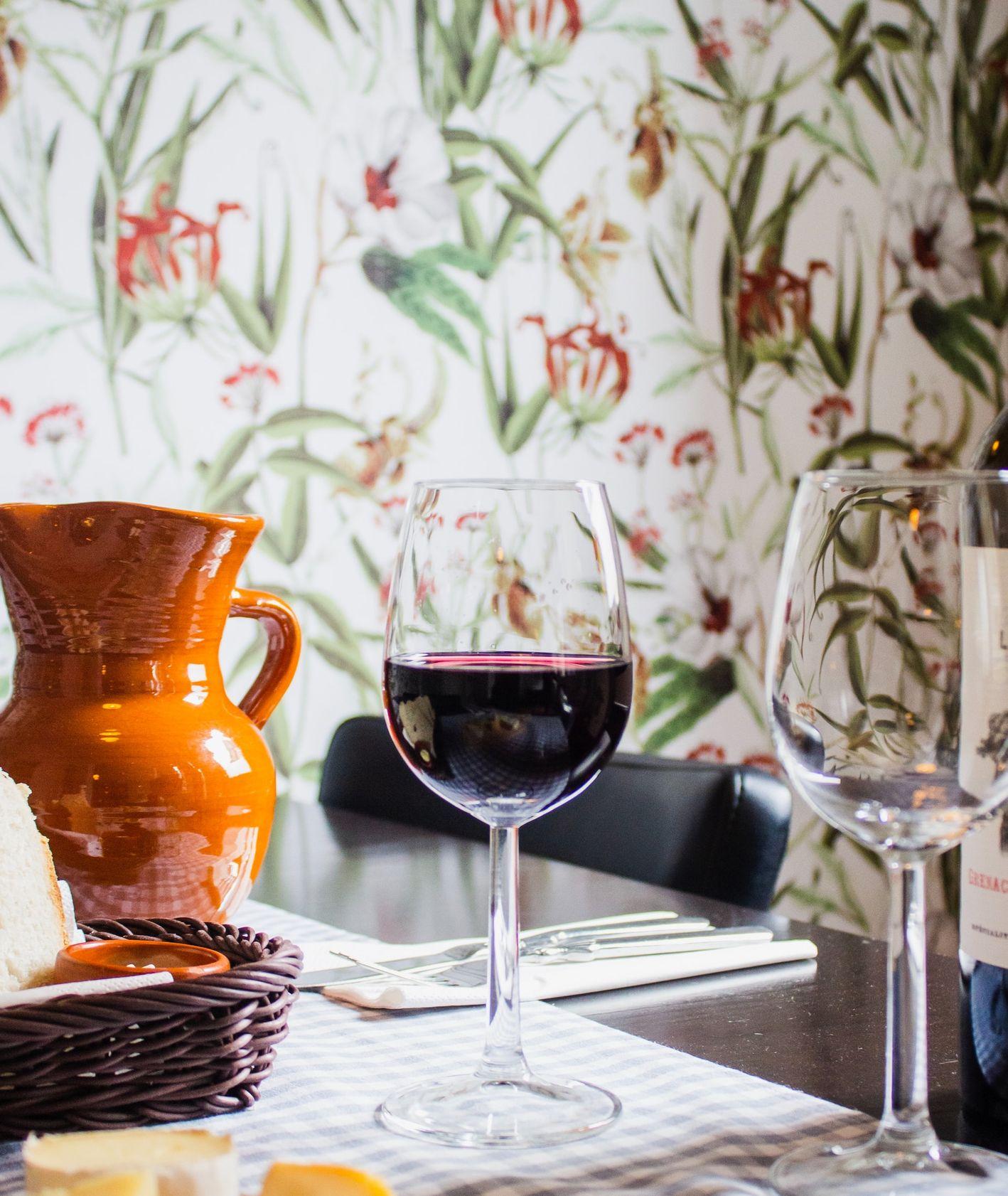Kieliszek czerwonego wina i deska serów (fot. Louis Hansel / unsplash.com)