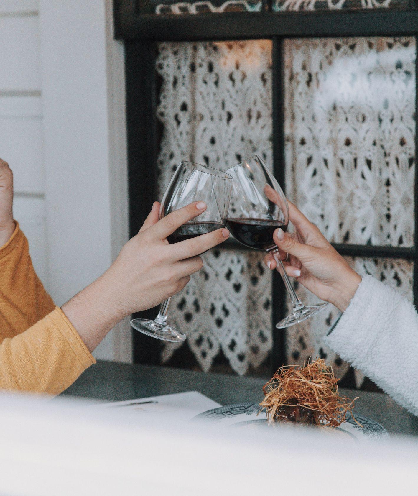 Para stukająca się kieliszkami z czerwonym winem w restauracji (fot. Nate Johnston / unsplash.com)
