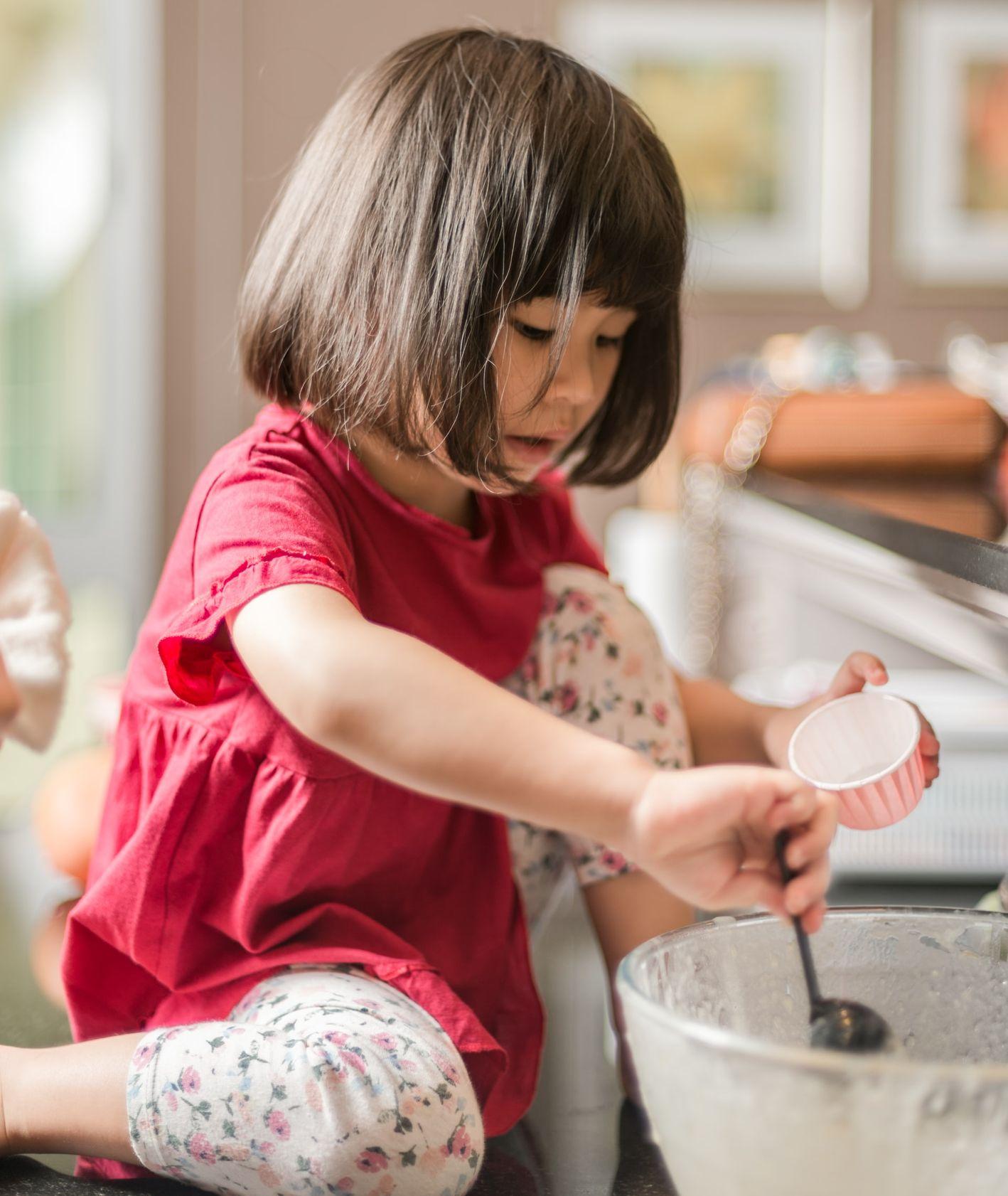 Dziewczynka mieszająca ciasto, dzieci w kuchni, wspólne gotowanie (fot. Tanaphong Toochinda / unsplash.com)