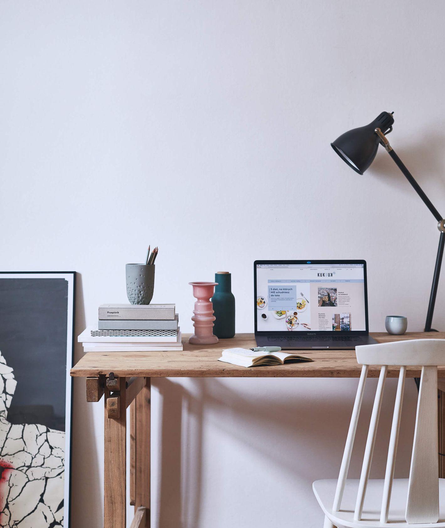 Przygotowane do pracy biurko, na nim laptop, lampka, książki, notes (fot. Maciej Niemojewski)