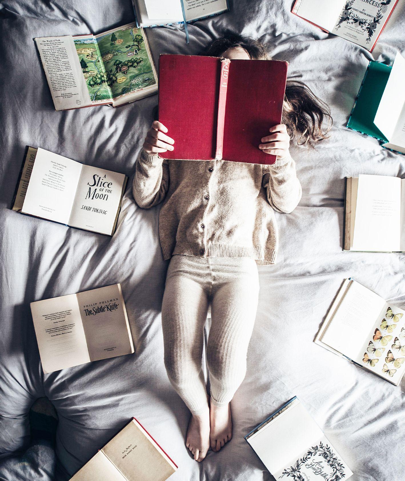 Dziewczynka czytająca na łóżku książki z pięknymi ilustracjami (fot. Annie Spratt / unsplash.com)