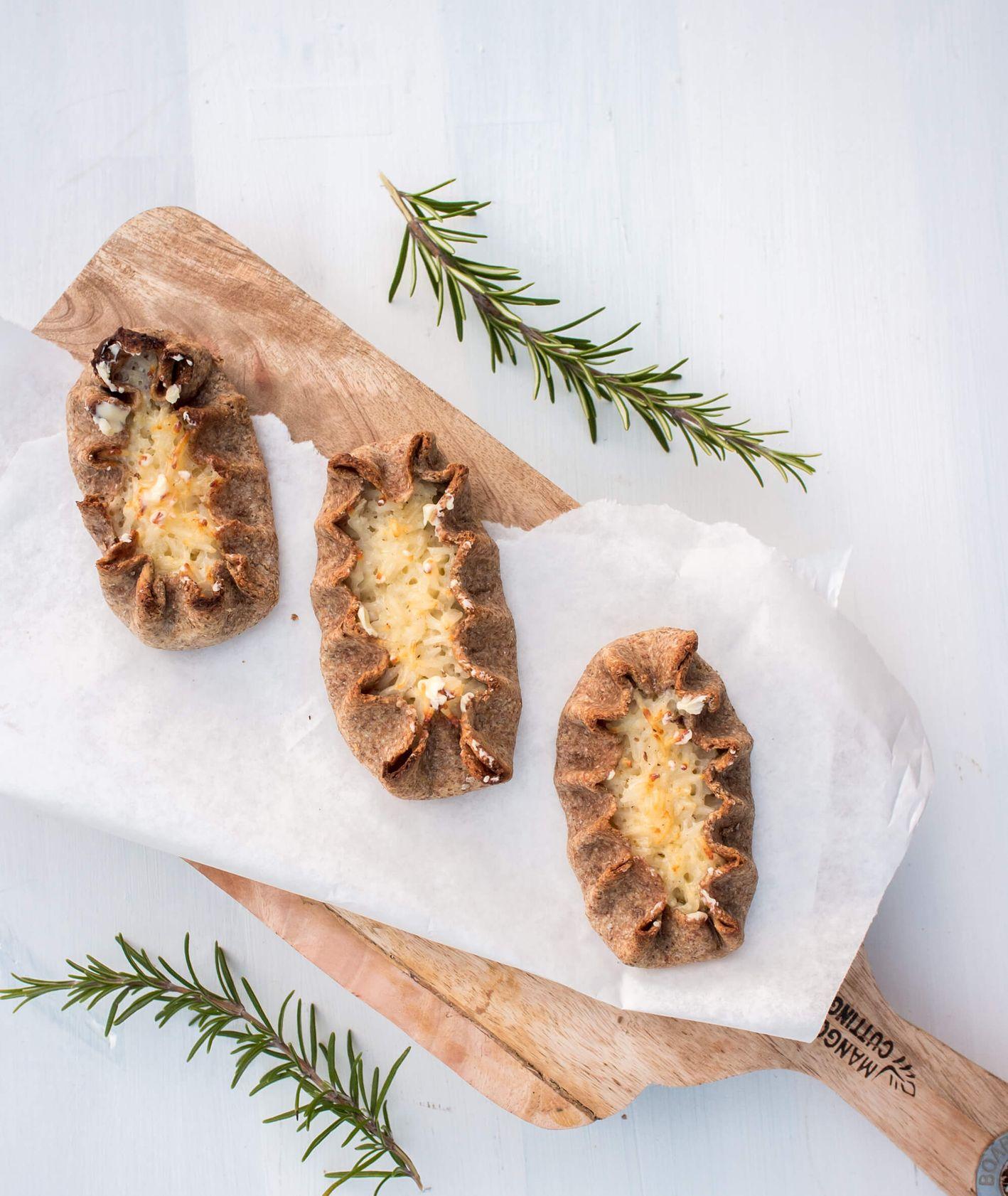 Fińskie pierogi karelskie – Karjalanpiirakka, upieczone w piekarniku, polane roztopionym masłem