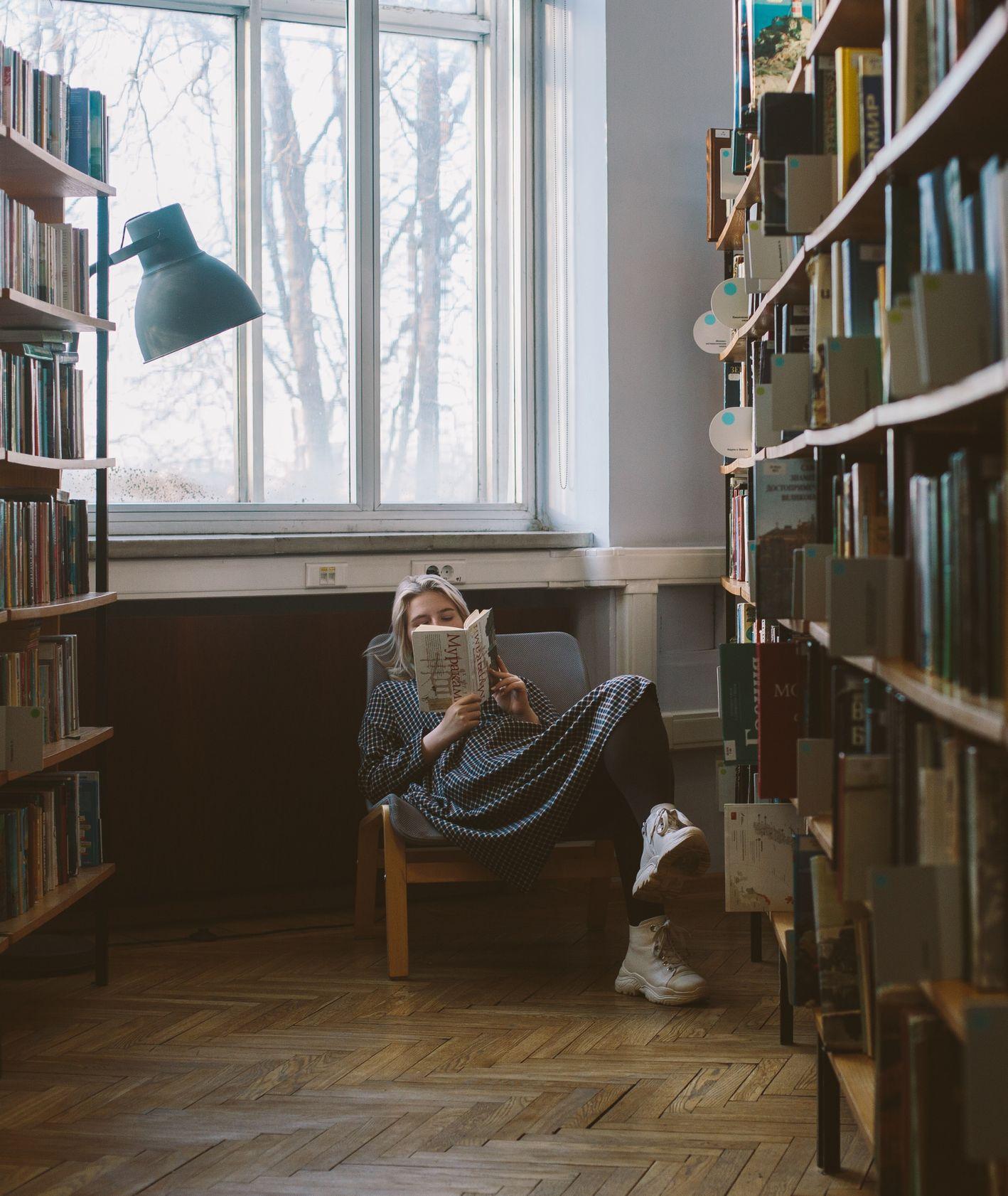 Kobieta czyta książkę w fotelu przy oknie (fot. Polina Zimmerman)