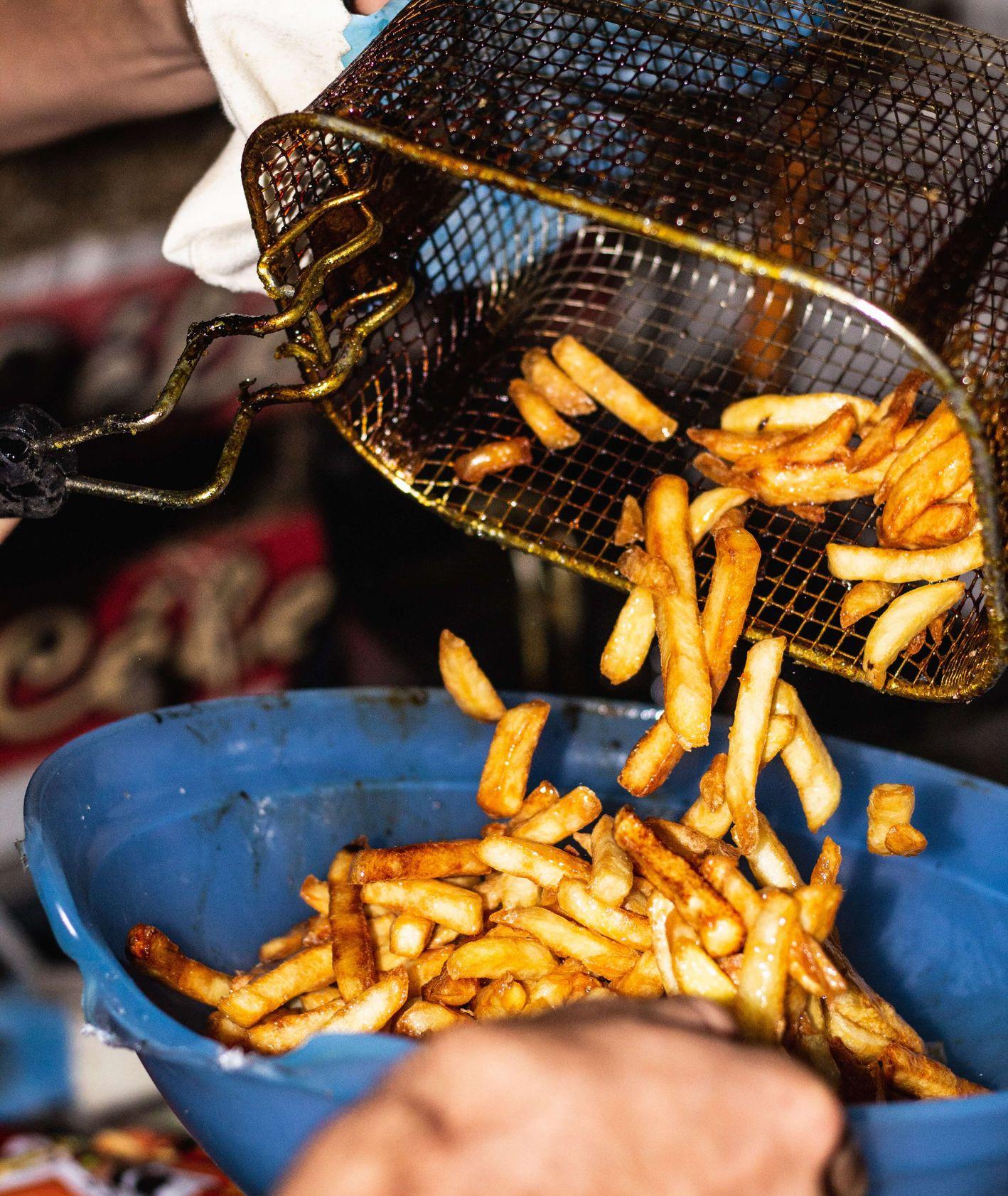 Frytki wysypywane z frytkownicy, fast food (fot. Lucas Mellec)