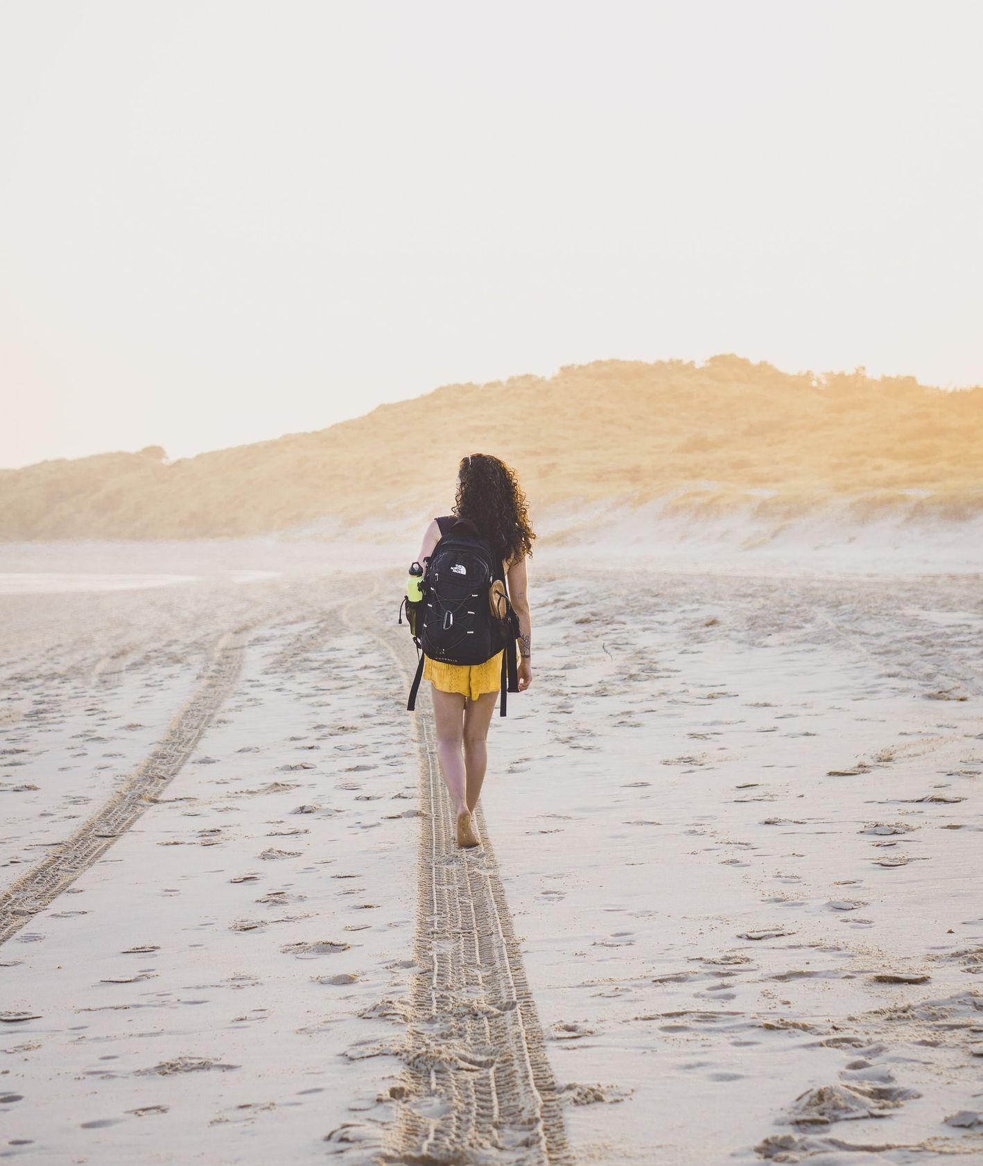 Kobieta z plecakiem idąca plażą (fot. Amy Fraser / unsplash.com)